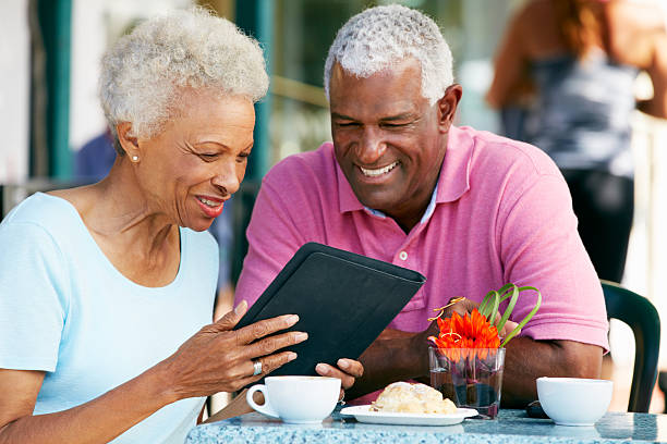senior couple using tablet computer at outdoor café - eating technology stock photos and pictures