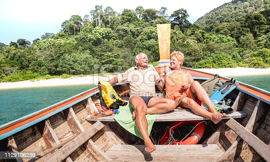 istock Senior couple vacationer relaxing at island hopping tour after beach exploration during snorkel boat trip in Thailand - Active elderly and travel concept on tour around world - Warm day bright filter 1129106239