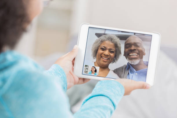 Senior couple video chatting on granddaughter's device screen A senior couple laugh as they video chat from the screen of their unrecognizable granddaughter's digital tablet screen.  She hold's the tablet with both hands. long distance relationship stock pictures, royalty-free photos & images