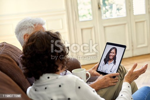 Senior couple video conferencing with doctor through digital tablet in living room. Retired elderly man and woman are sitting on sofa. They are at home.