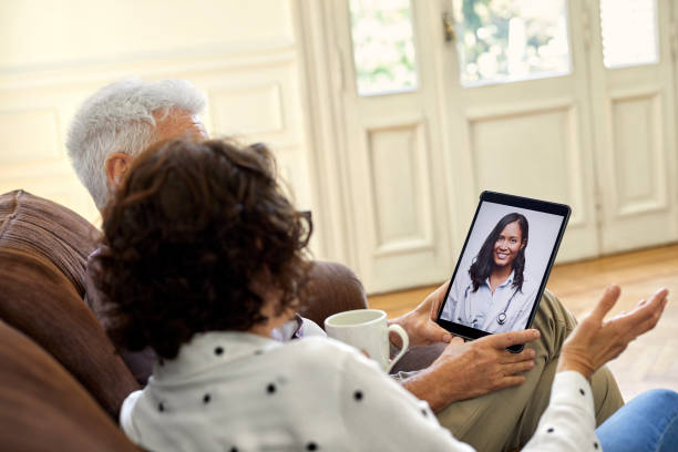videoconferencia de pareja senior con médico - telehealth fotografías e imágenes de stock