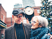 Senior couple visiting Outdoor Christmas market during Holidays. Main street clock tower and large Christmas tree behind them.