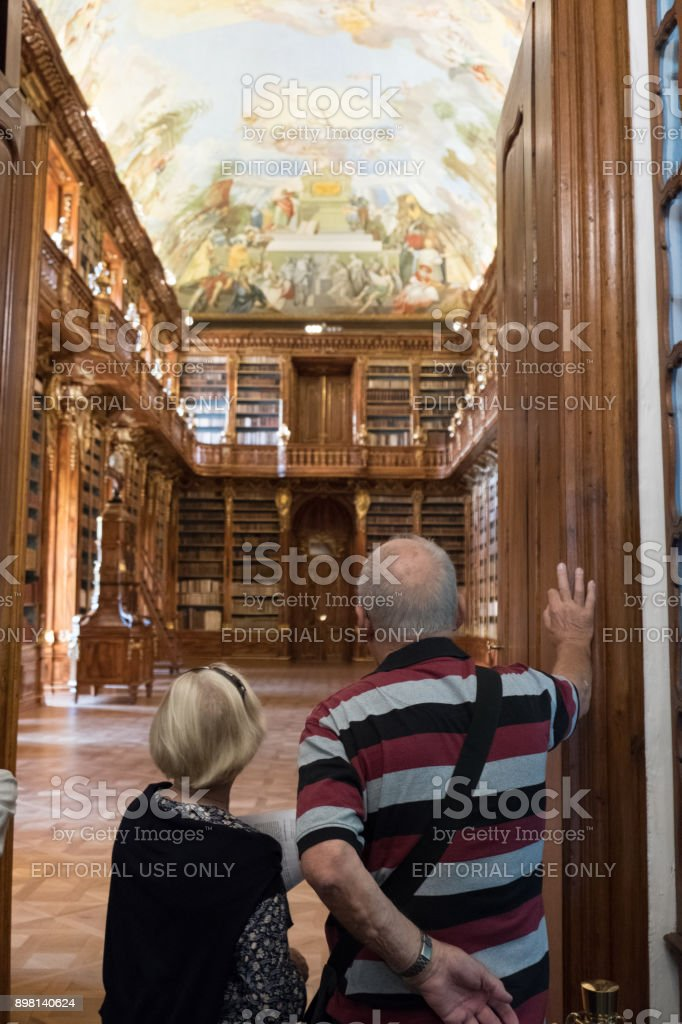 Senior couple visiting the Library of the Strahov Monastery. Couple stand at the doorway of Philosophical Hall looking at the 300 year old library in Prague. stock photo