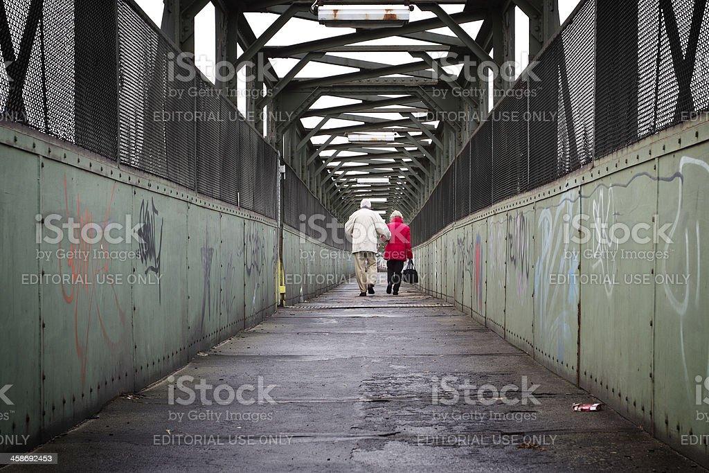 Senior couple walking across a train bridge royalty-free stock photo