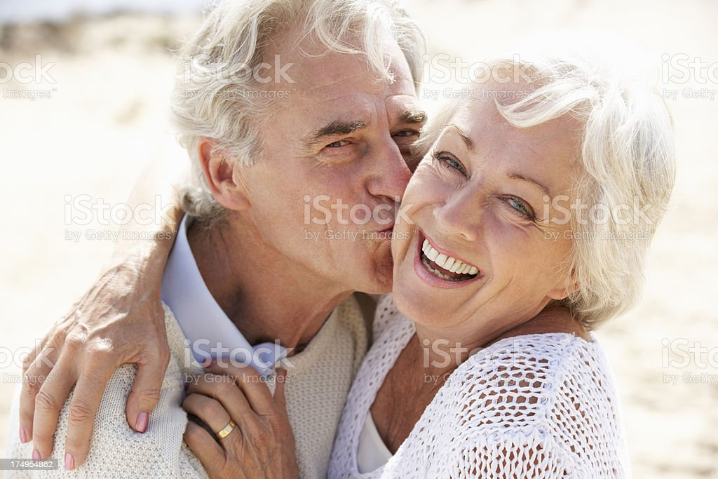 Senior Couple Walking Along Beach Together stock photo