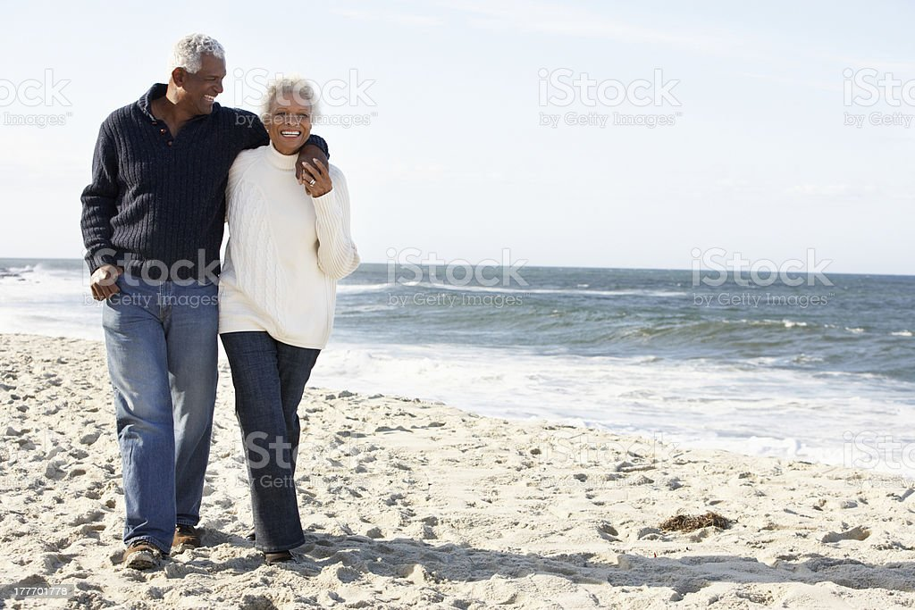 Senior Couple Walking Along Beach Together stock photo