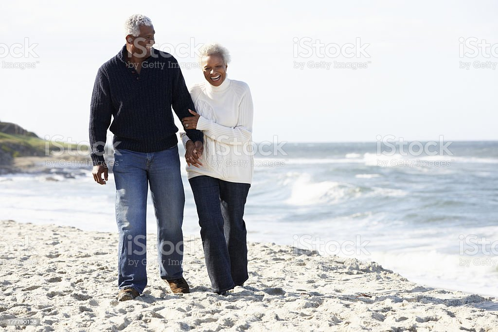 Senior couple walking along the beach while holding hands stock photo