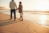 Rear view of a senior couple walking along the sea shore. Mature man and woman together strolling on the sea shore at sunset.