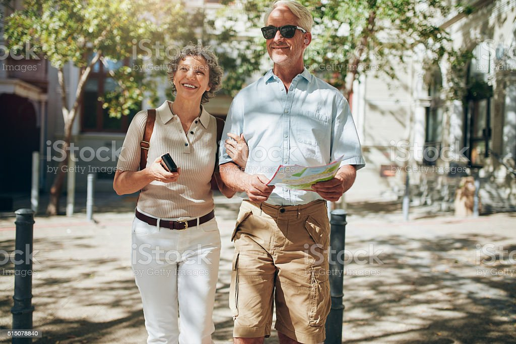 Senior couple walking around the city holding a map stock photo