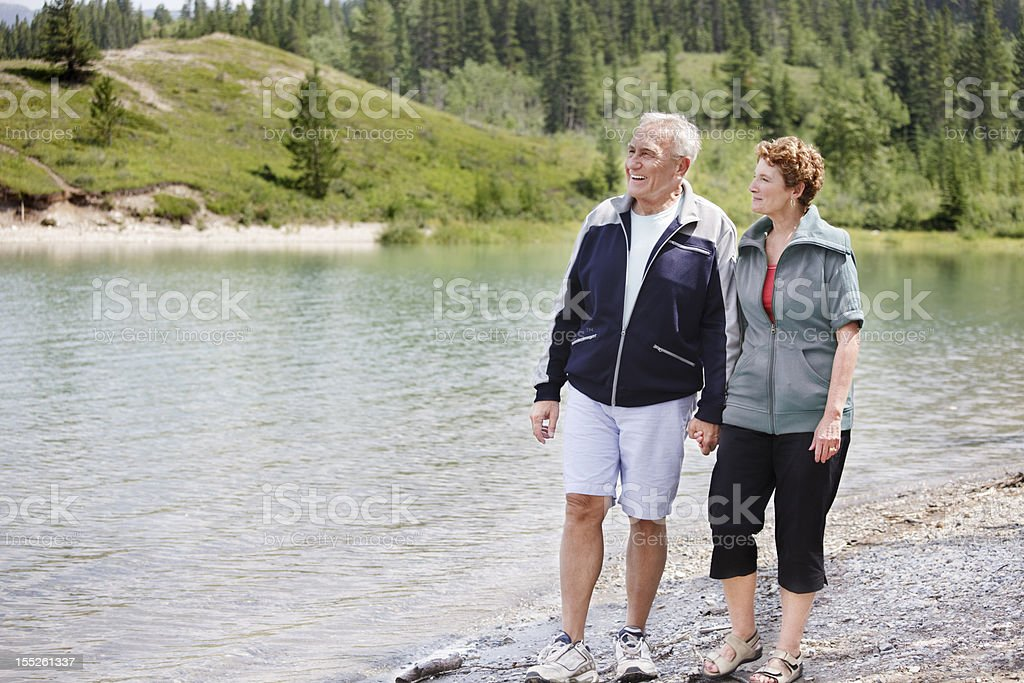 Senior couple walking by the lake stock photo