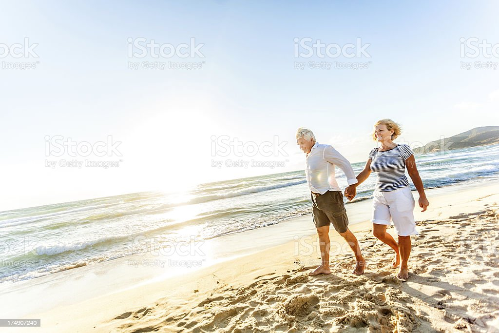 Senior couple walking by the sea royalty-free stock photo