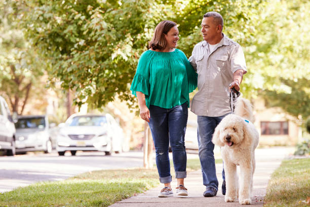 Senior Couple Walking Dog Along Suburban Street stock photo
