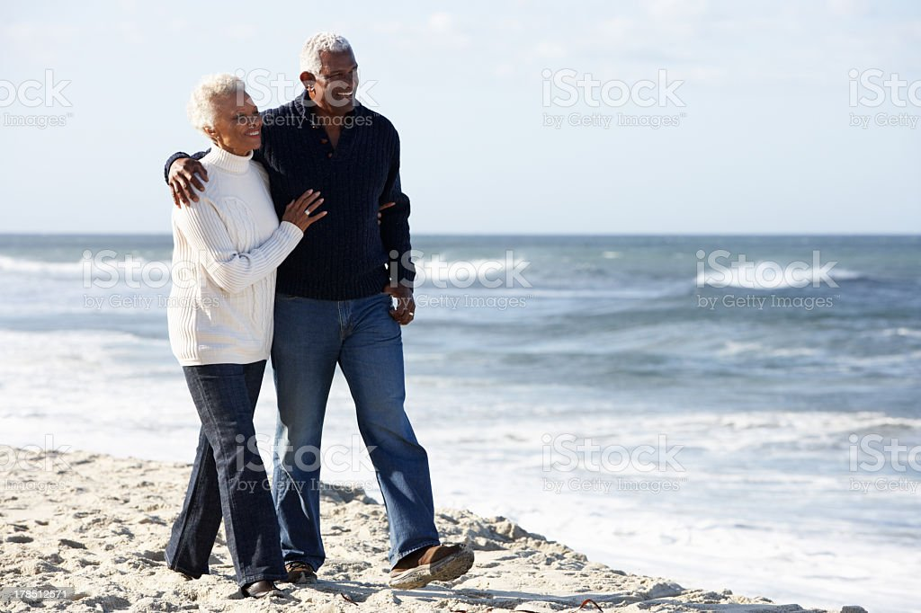 Senior couple walking down the beach stock photo