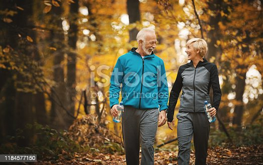 Closeup front view of a senior couple walking in a forest and having fun. They are enjoying these beautiful fall colors while stepping over dry leaves and sipping water from water bottles.