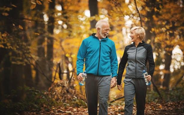 starsza para spacerująca po lesie. - wędrować zdjęcia i obrazy z banku zdjęć