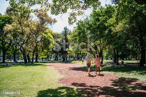 Senior heterosexual couple walking in public park holding hands.