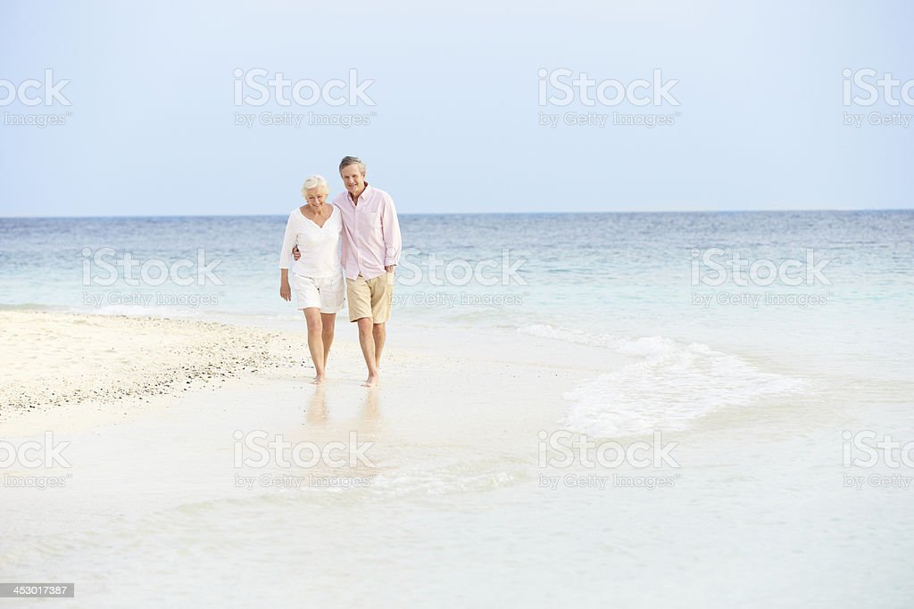 A senior couple walking on a beach royalty-free stock photo