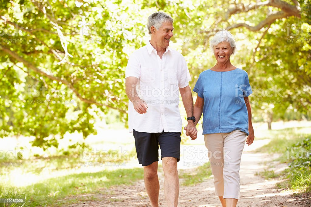 Senior couple walking on a path together in the countryside stock photo