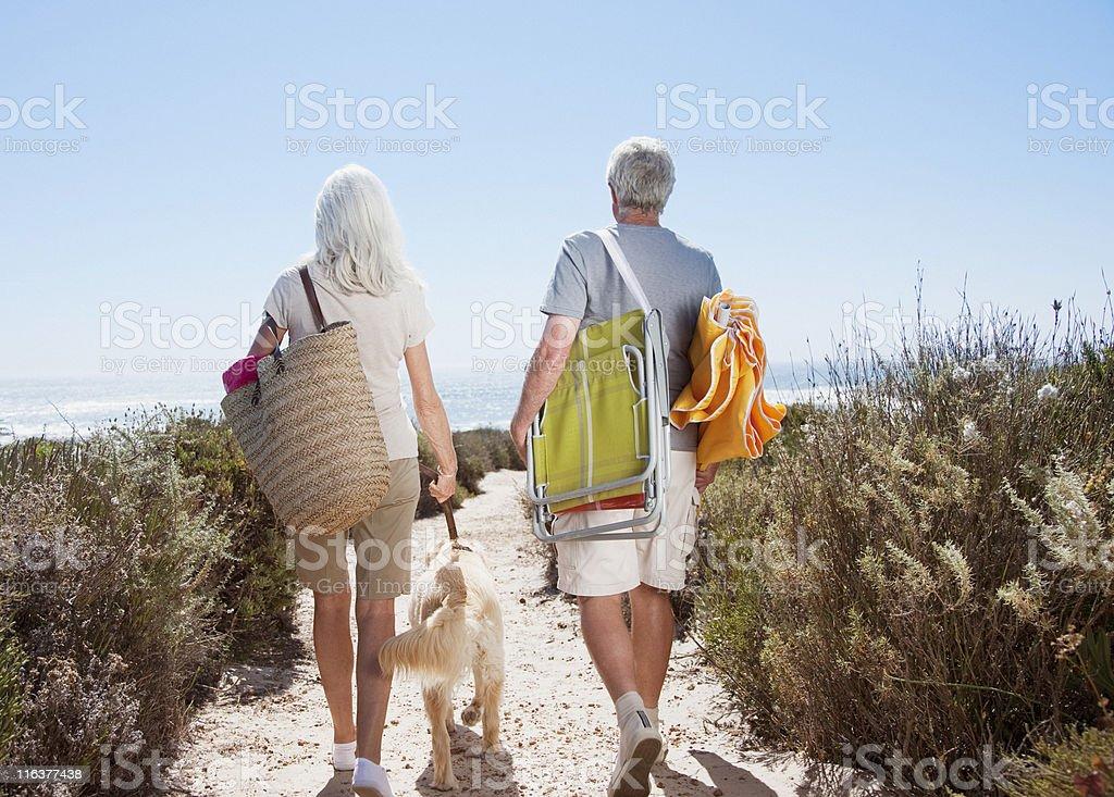 Senior couple walking on beach path with dog stock photo