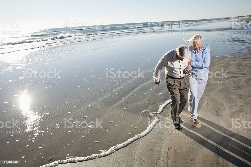 Senior couple walking on beach royalty-free stock photo