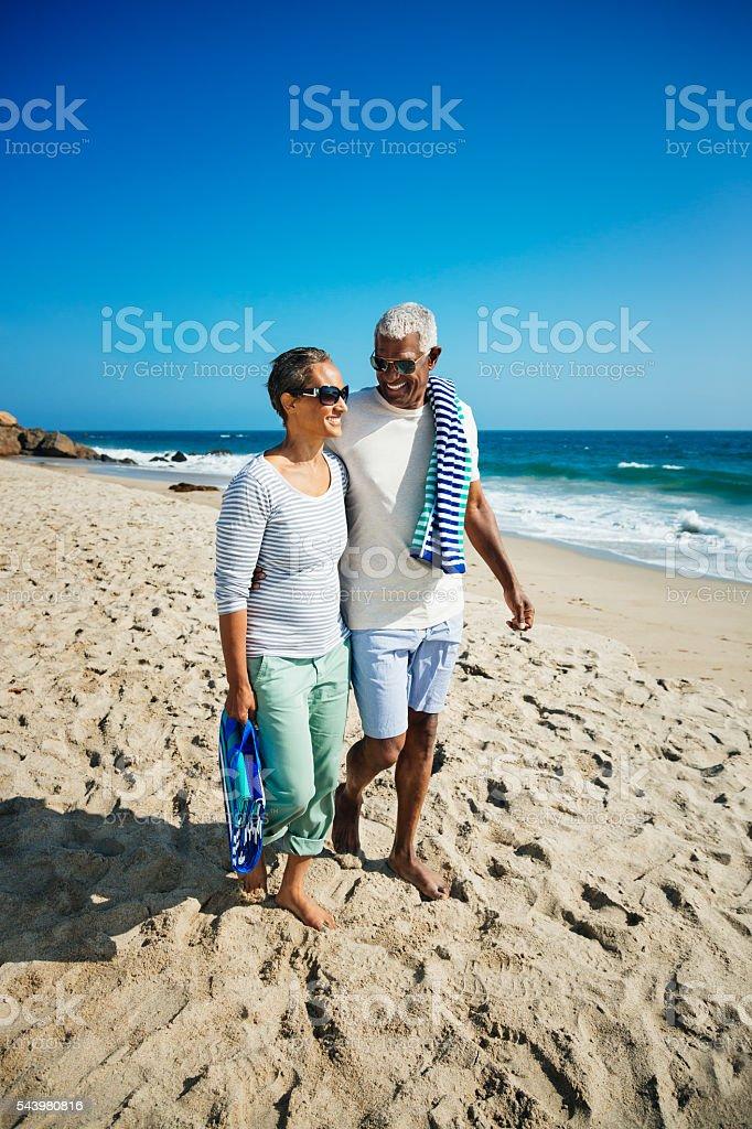 Senior couple walking on beach stock photo