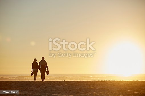Full length rear view of senior couple walking on beach during sunset
