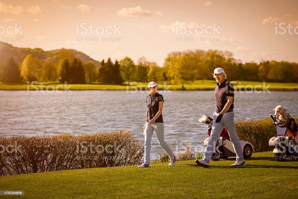 Senior couple marchant sur le parcours de golf. - Photo