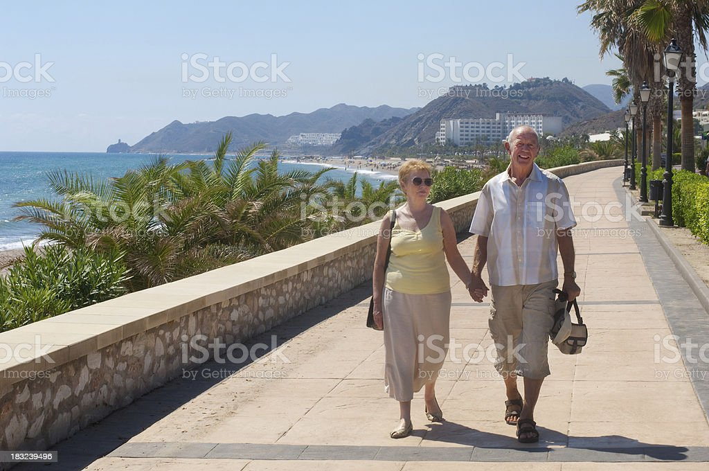 senior couple walking on holiday or are they expatriates stock photo