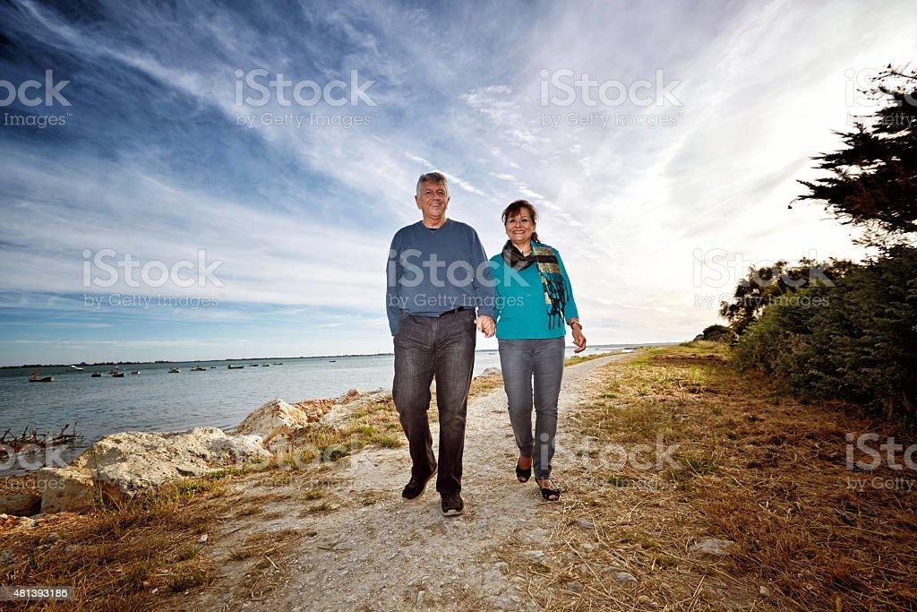 Senior couple walking on seashore footpath stock photo