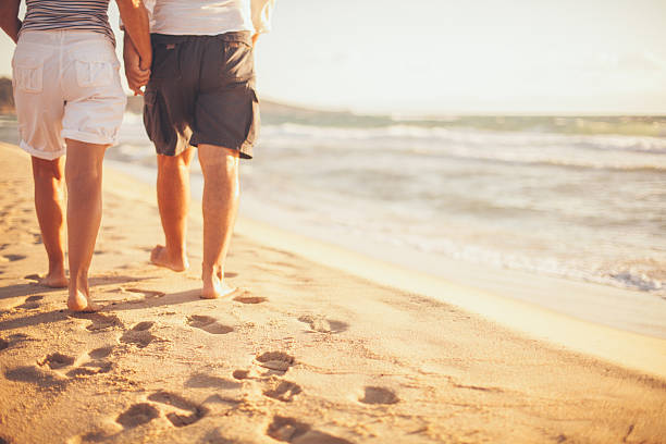 Senior couple walking on the beach stock photo