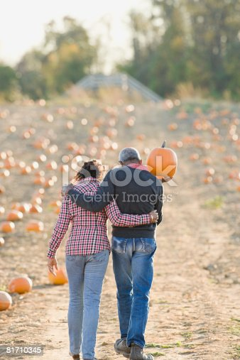 81711567 istock photo A senior couple walking through a field of pumpkins 81710345