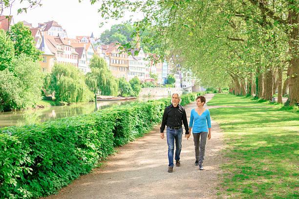 senior paar beim gehen durch einen park, tübingen, deutschland - sommerferien baden württemberg stock-fotos und bilder