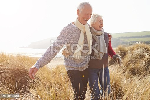 istock Senior Couple Walking Through Sand Dunes On Winter Beach 501948853