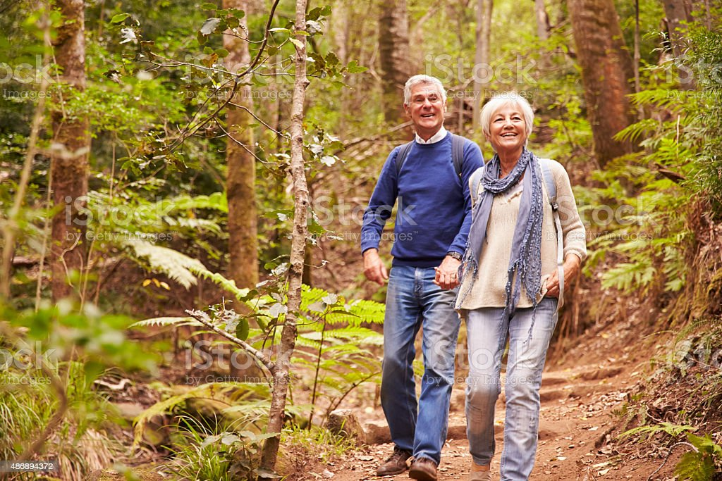 Senior couple walking together in a forest​​​ foto
