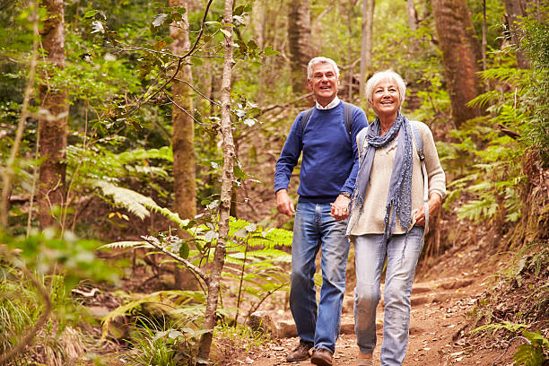 senior couple walking together in a forest - aktiva pensionärer utflykt bildbanksfoton och bilder