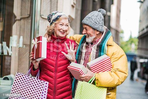 817549606 istock photo Senior couple walking with Christmas shopping bags 1189339838