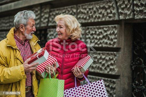 817549606 istock photo Senior couple walking with shopping bags 1184888429