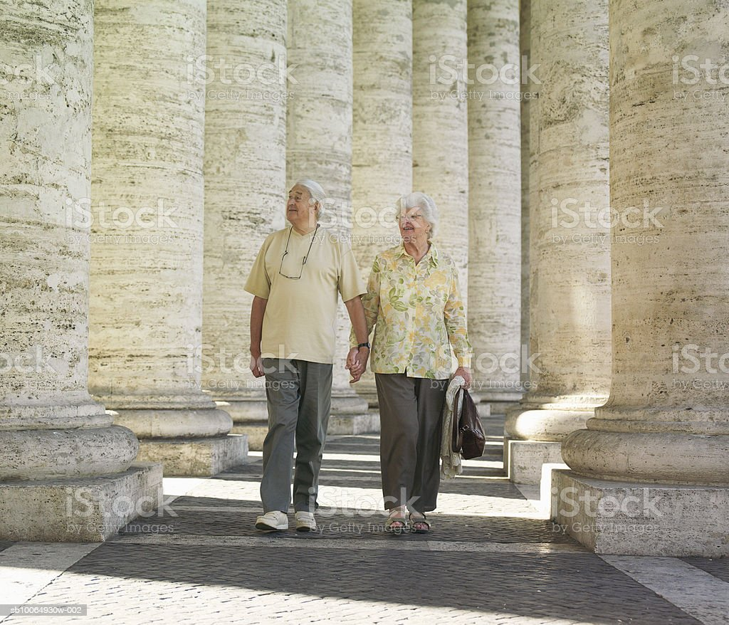 Senior couple watching columns, holding hands foto de stock libre de derechos