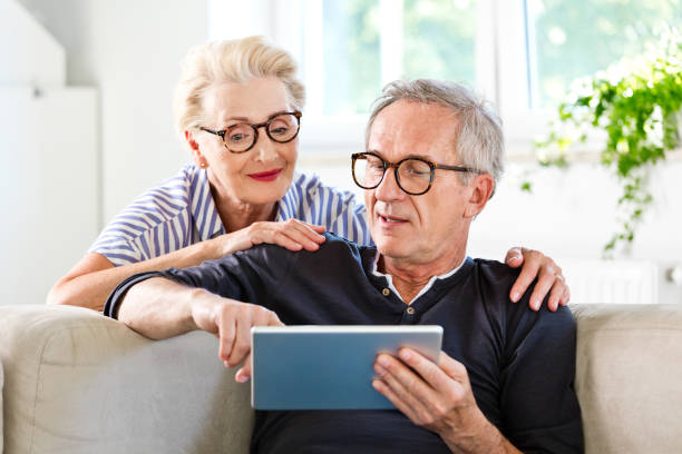 Senior couple watching digital tablet together at home stock photo