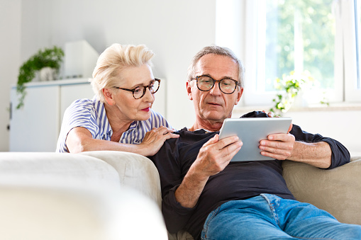 Elderly man sitting on sofa in the living room at home and showing something on digital tablet his wife. Senior woman peeking on screen.