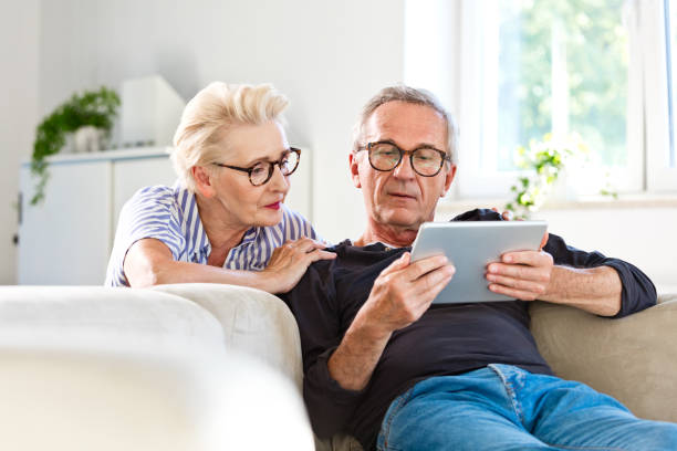 Senior couple watching digital tablet together at home Elderly man sitting on sofa in the living room at home and showing something on digital tablet his wife. Senior woman peeking on screen. husband stock pictures, royalty-free photos & images