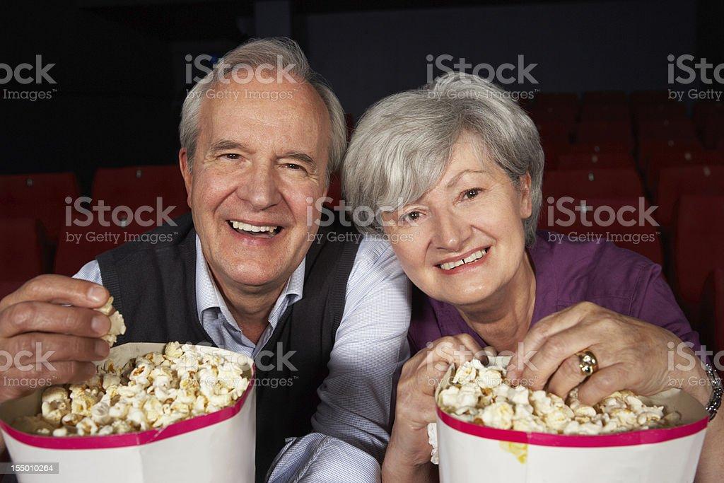 Senior Couple Watching Film In Cinema stock photo