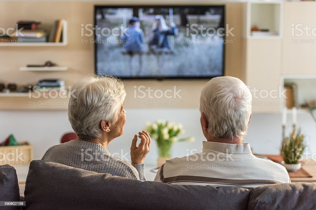 Senior couple watching television show stock photo