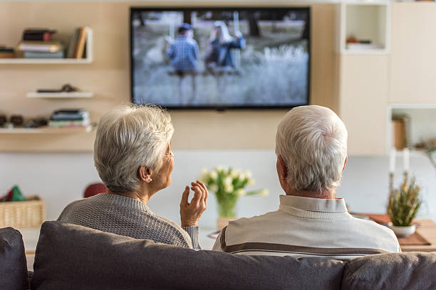 Senior couple watching television show Senior couple sitting on sofa and watching television show at home. watching tv stock pictures, royalty-free photos & images