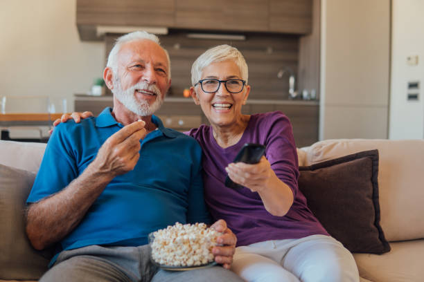Senior couple watching TV Elderly couple eating popcorn and watching TV together watching tv stock pictures, royalty-free photos & images
