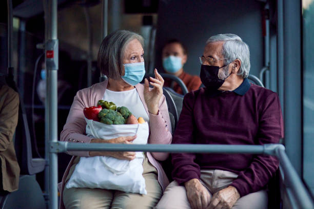 Senior couple wearing covid mask holding groceries bag inside bus stock photo
