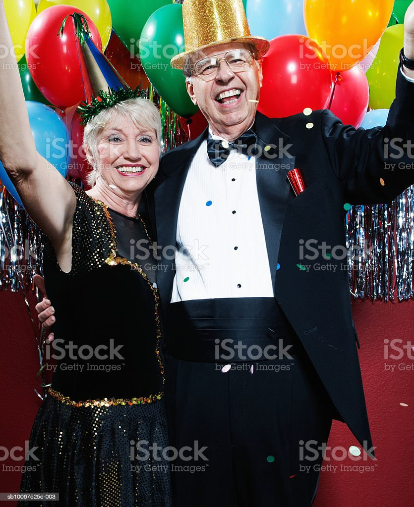 Senior couple wearing party hats celebrating New Years Eve, smiling foto de stock libre de derechos