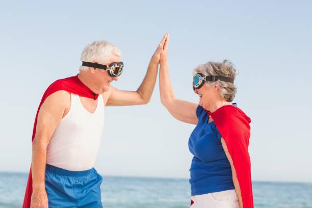 älteres paar tragen superman-kostüm - 70 jahre kleidung stock-fotos und bilder