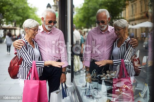 Senior couple somewhere in the city carrying shopping bags while window shopping.