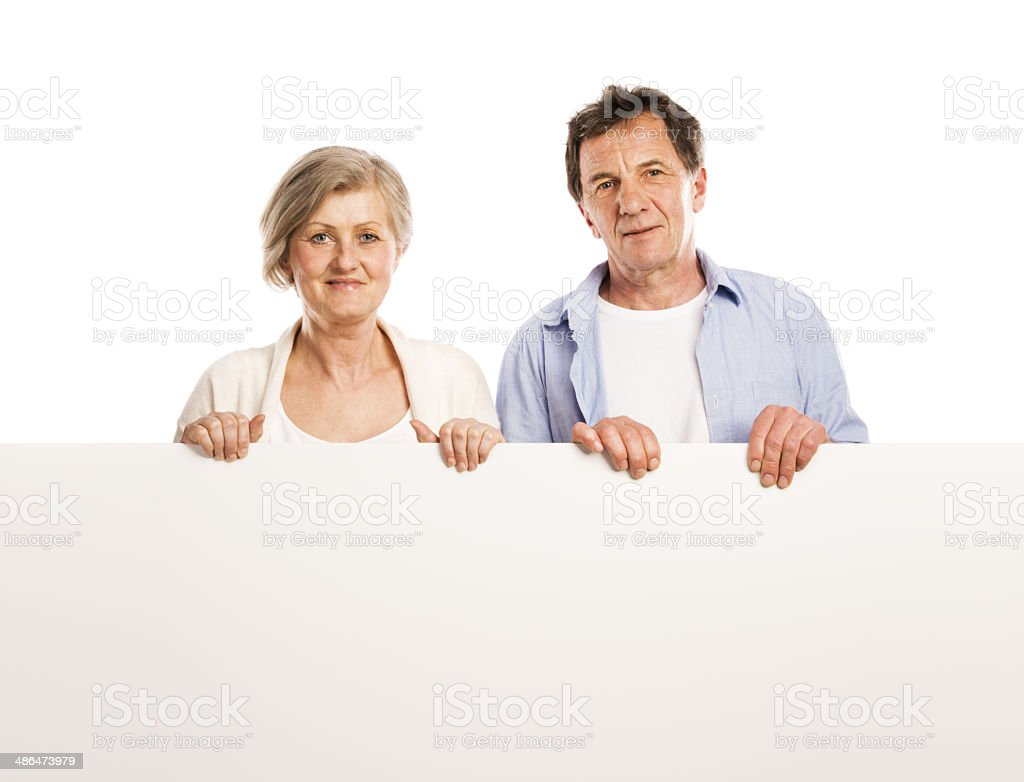 Senior couple with advertising board royalty-free stock photo